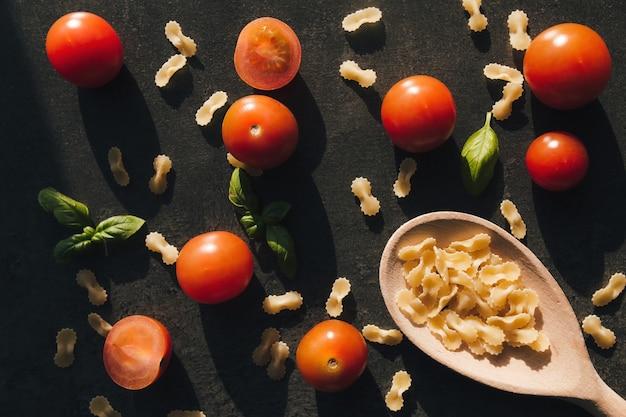 Czerwone pomidory koktajlowe, zielona bazylia, makaron wermiszel motylkowy, drewniana łyżka.