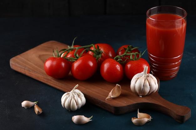 Czerwone pomidory, rękawiczki czosnkowe i szklankę soku pomidorowego na niebieskim tle.