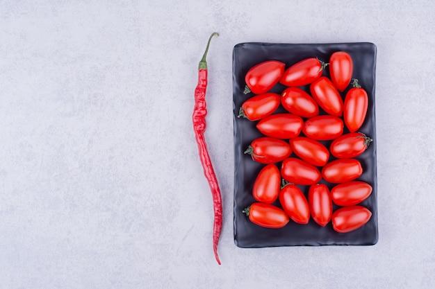 Czerwone pomidory w czarnej półmisku z papryką chili