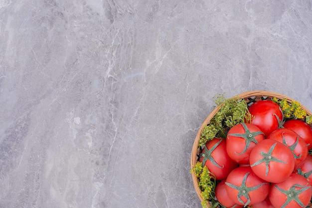 Czerwone pomidory w drewnianym talerzu na marmurze
