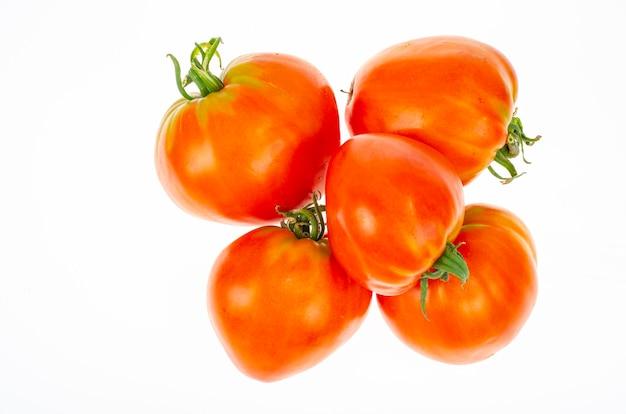 Czerwone pomidory w kształcie serca na białym tle. zdjęcie studyjne.