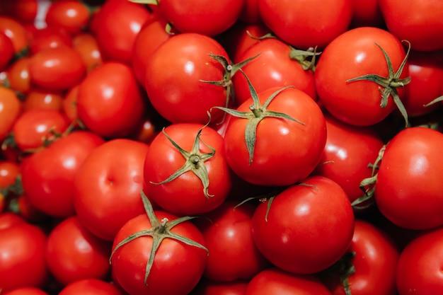 Czerwone pomidory. warzywa układa się jeden na drugim.