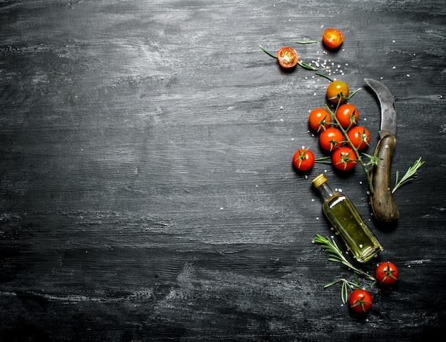 Czerwone pomidory z rozmarynem i butelką oliwy z oliwek. na czarnym tle rustykalnym.