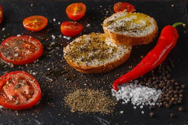 Czerwone pomidory z rozmarynem i oliwą z oliwek. na czarnej rustykalnej powierzchni
