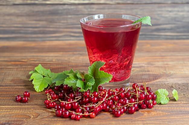 Czerwone porzeczki i zielone liście na ciemnym tle. koktajl witaminowy.