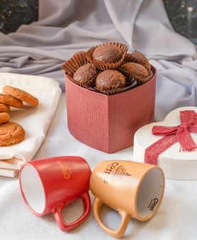 Czerwone pudełko czekoladowych pralinek z pustymi filiżankami kawy na stole.