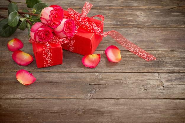 Czerwone pudełko i bukiet róż na drewnianym stole