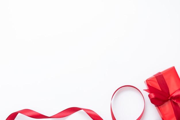 Czerwone pudełko i czerwoną wstążką na białym tle. świąteczna makieta.