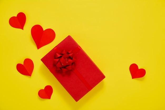 Czerwone pudełko i czerwone serca papieru na żółtym tle koncepcja walentynki dla miłości miejsca na tekst