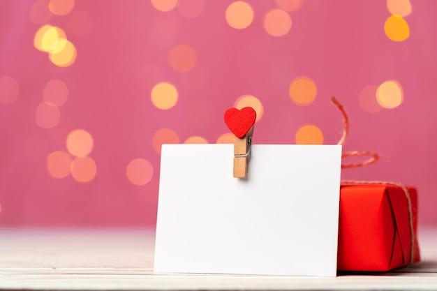 Czerwone pudełko i kartkę z życzeniami na różowym tle z bliska