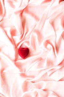Czerwone pudełko na biżuterię w kształcie serca na różowym jedwabiu walentynki prawdziwa miłość zaręczyny i propozycja c...