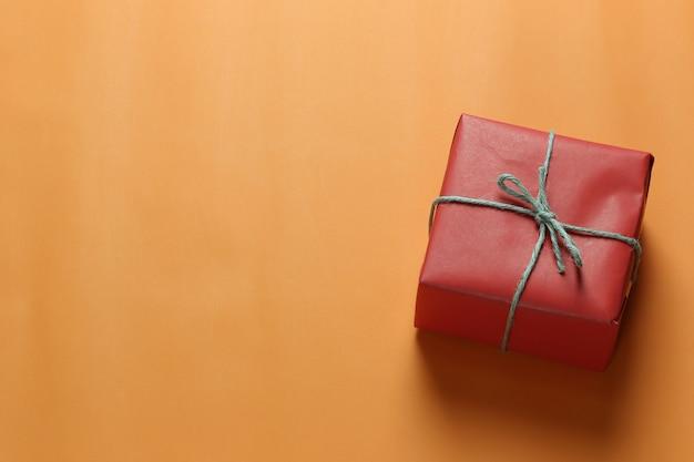 Czerwone pudełko na boże narodzenie umieszczone na pomarańczowej podłodze sztuki papieru i miejsce na kopię.