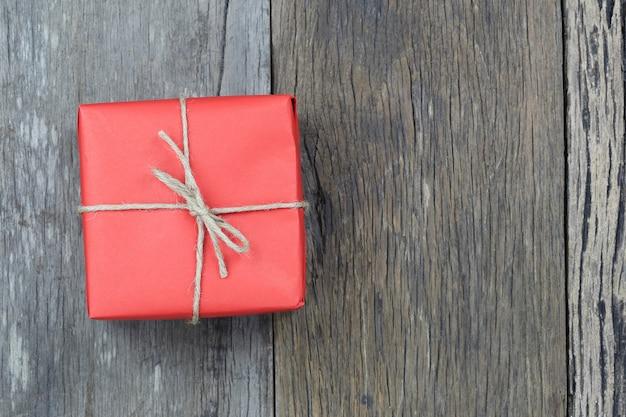 Czerwone pudełko na drewnianej podłodze i miejsce na kopię.
