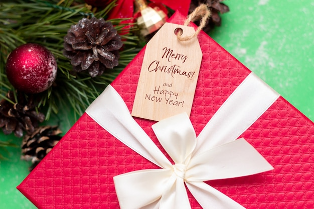 Czerwone pudełko na prezent drewniana notatka z tekstem wesołych świąt i szczęśliwego nowego roku gałąź jodły