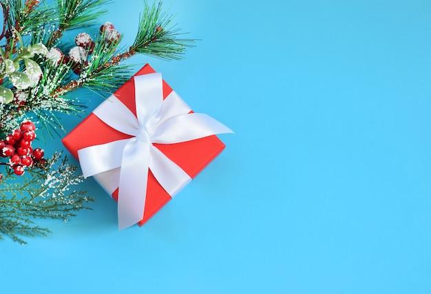 Czerwone pudełko na prezent na boże narodzenie z białą kokardą i gałęziami choinki.