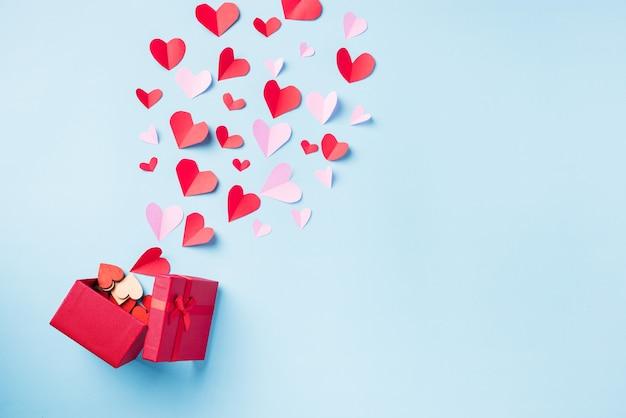 Czerwone pudełko na prezent pocztówka i papierowe latające elementy serca wycinają kartkę z życzeniami