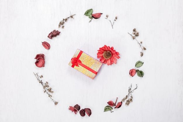 Czerwone pudełko na prezenty w świątecznej okrągłej ramie wykonane z naturalnych zimowych rzeczy