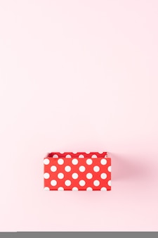 Czerwone pudełko na różowej powierzchni.