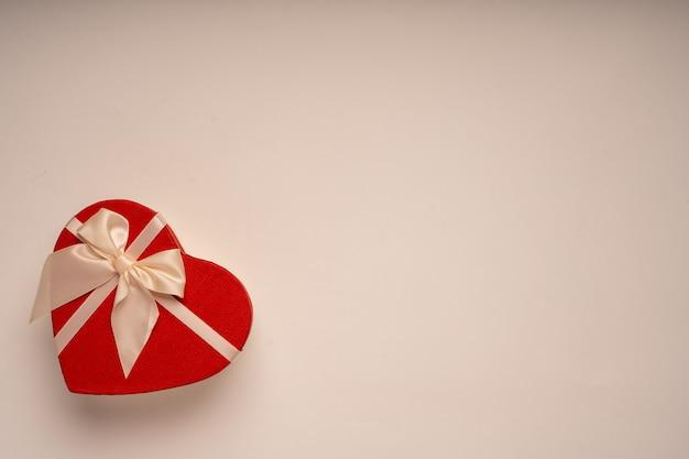 Czerwone pudełko prezentowe, forma serca, przewiązane wstążką, gratulacje, prezent, święto, niespodzianka