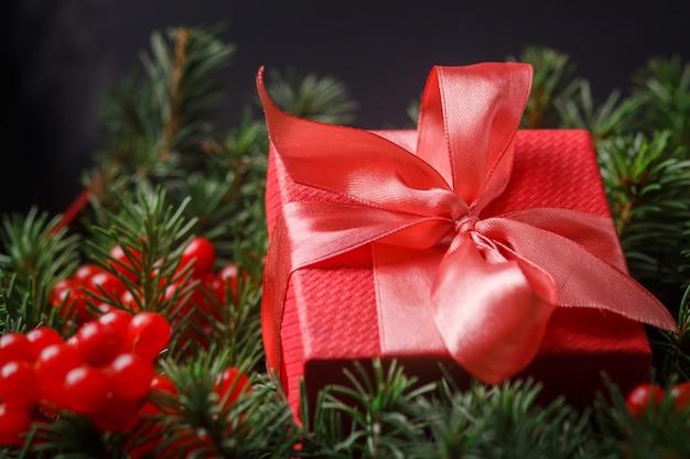 Czerwone pudełko prezentowe z satynową różową kokardką, zanurzone w igłach choinki ozdobionej czerwonymi jagodami.