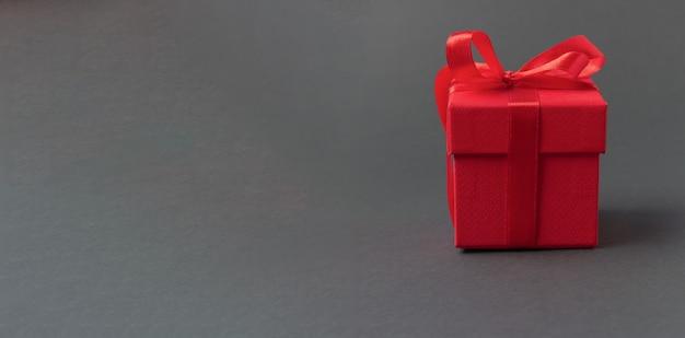 Czerwone pudełko przewiązane wstążkami z kokardkami na szarym tle