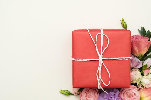 Czerwone pudełko upominkowe i asortyment kwiatów. leżał na płasko.