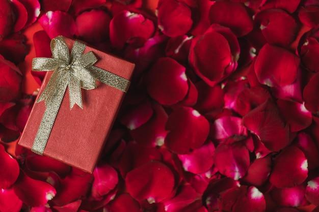Czerwone pudełko upominkowe umieszczone na czerwonych płatkach róży widok z góry, motyw walentynkowy