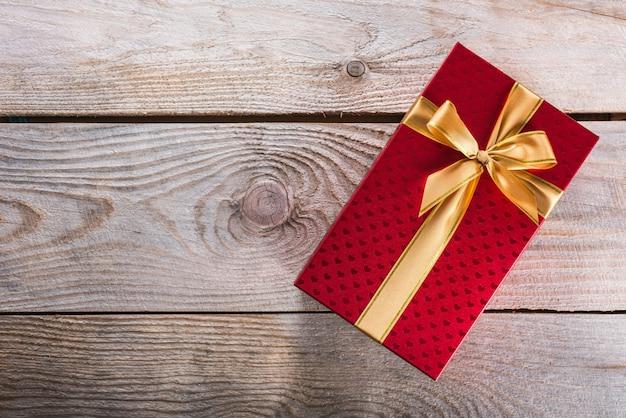 Czerwone pudełko upominkowe związane złotą jedwabną wstążką