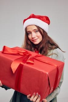 Czerwone pudełko w dłoni z piękną dziewczyną w świątecznych czapkach