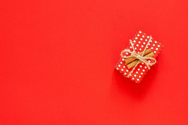 Czerwone pudełko w kropki z cynamonem na czerwonym tle, koncepcja wesołych świąt i szczęśliwego nowego roku