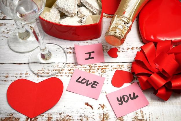 Czerwone pudełko w kształcie serca, butelka szampana i dwie szklanki