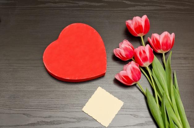 Czerwone pudełko w kształcie serca, czysta karta, różowe tulipany. czarny stół. widok z góry, miejsce na tekst