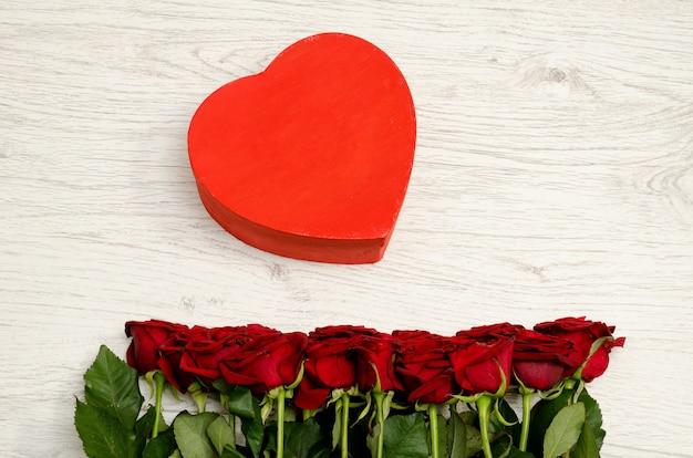 Czerwone pudełko w kształcie serca i róże na biały drewniany, widok z góry