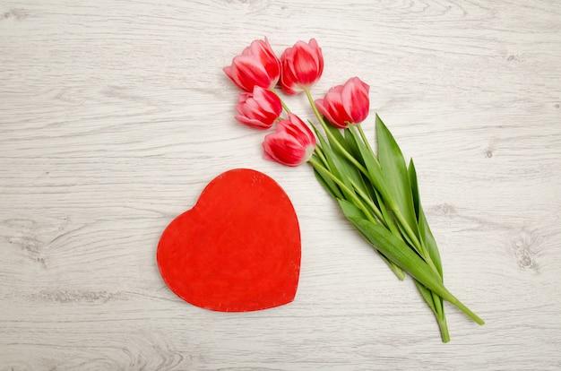 Czerwone pudełko w kształcie serca i różowe tulipany na jasnym drewnianym stole. widok z góry
