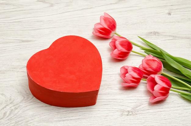 Czerwone pudełko w kształcie serca i różowe tulipany na jasnym drewnie. miejsce na tekst