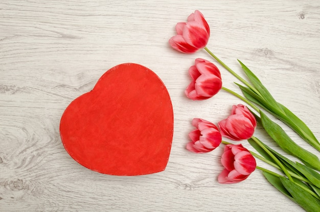 Czerwone pudełko w kształcie serca i różowe tulipany