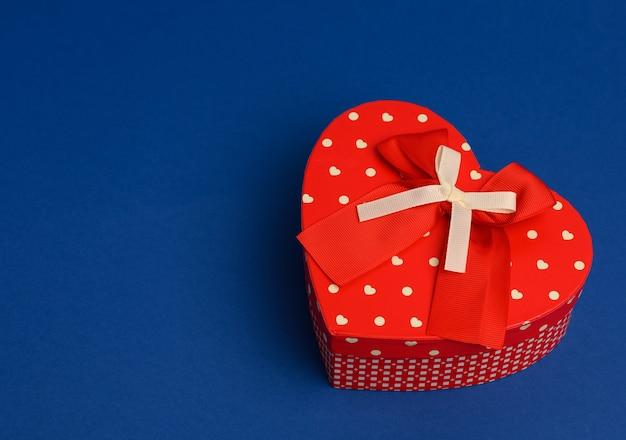 Czerwone pudełko w kształcie serca na niebieskim tle, z bliska