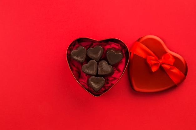 Czerwone pudełko w kształcie serca z cukierkami czekoladowymi