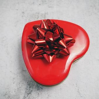 Czerwone pudełko w kształcie serca z kokardą na szarym tle, widok z góry