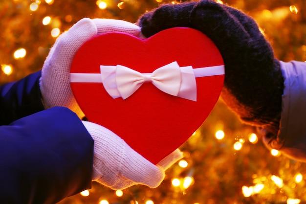 Czerwone pudełko w kształcie serca z kokardą w dłoniach nad oświetloną powierzchnią