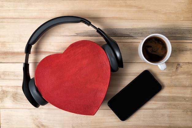 Czerwone pudełko w kształcie serca ze słuchawkami, smartfonem i kawą na drewnie. muzyka z miłością koncepcja.