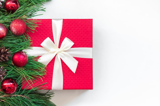 Czerwone pudełko w pobliżu gałęzi choinki z zabawkami kulkami i szyszkami na białym tle