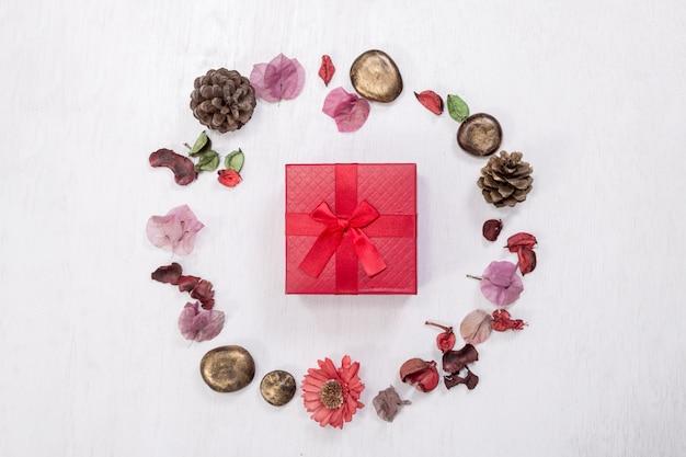 Czerwone pudełko w świątecznej oprawie z naturalnych zimowych rzeczy