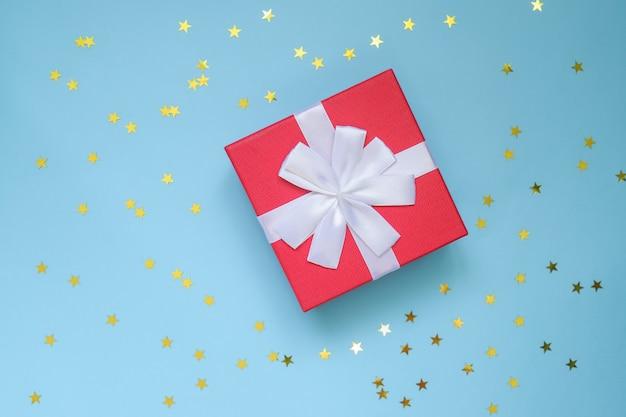 Czerwone pudełko z białą kokardą na niebiesko-białej ścianie z konfetti w kształcie gwiazdy. świąteczna kartka z pozdrowieniami. koncepcja wakacje.