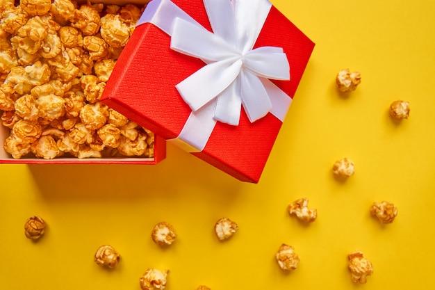 Czerwone pudełko z białą kokardą pełną smacznego karmelowego popcornu na żółtym tle.