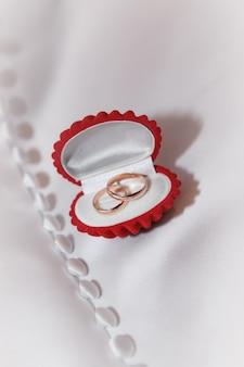 Czerwone pudełko z biżuterią ze złotymi obrączkami na białej tkaninie