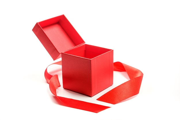 Czerwone pudełko z czerwoną wstążką na białym tle. otwarte pudełko ze sklepu jubilerskiego.