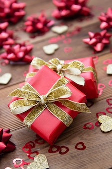 Czerwone pudełko z kokardkami, na drewnianym stole. skopiuj miejsce walentynki, urodziny, boże narodzenie.