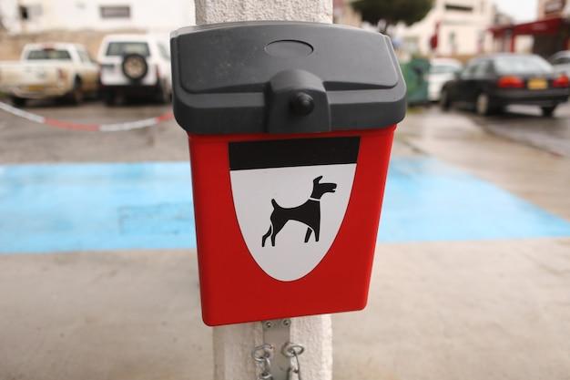 Czerwone pudełko z paczkami dla psów kupa na zewnątrz