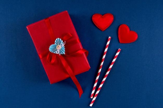 Czerwone pudełko z papierową słomką w kształcie serca i kokardy na klasycznym niebieskim tle w kolorze 2020. koncepcja opakowania walentynki 14 lutego. leżał z płaskim, kopia przestrzeń, widok z góry.